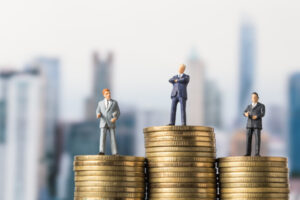miniature-model-group-investor-standing-coin-with-city-background_42892-53